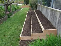 tiered raised bed against retaining wall