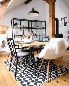 Esszimmer im Scandi-Style mit großem Esstisch, gemustertem Teppich, Ikea Vittsjö Regal und verschiedenen Designer-Stühlen.