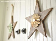 Wooden stars with paper fans hanging on a farmhouse hutch via Town and Country Living