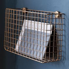Elevate magazines to a slick new level with a copper finish and iron wire grid basket that mounts to the wall with exaggerated hardware for modern effect. Holds coffee table reading in the living room, or scarves, mail, dog leashes and odds and ends in the entry.