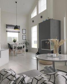 Viihtyisä ja valoisa olohuone, jonka keskellä takka jakaa ruokailutilan muusta osasta.