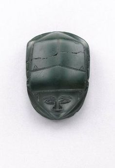 An Egyptian human-headed green jasper heart scarab - 2nd Intermediate Period, 13th Dynasty, circa 1786-1710 B.C. - Finely carved, the human face with a pointed chin, almond-shaped eyes, arching brows  tiny ears, the wing-case with a finely dotted line dividing it from the prothorax  another across the forehead, the two wing sectors each with tiny wing nicks  two small spirals at the back, the scarab legs carved with incised ridges indicating hairs, inscribed for 'Hatshepsut', 21/8in.  long,