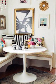 petite banquette, table à manger blanche et déco en coussins et tableaux