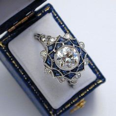Art Deco ring / vintage / Platinum ring with diamonds and sapphires Possibly France ca. 1925 The ring has a brilliant cut diamond of 1,25 cts in cased millegrain-setting, surrounded by 16 sapphires in a fancy cut and eight brilliant cut diamonds, also in millegrain-setting. Four more diamonds on the shank. Extraordinary design