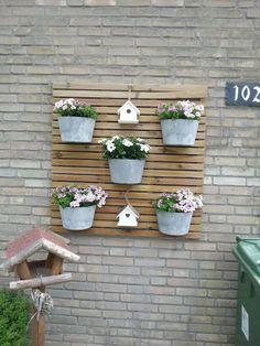 Gezien op facebook. Houten tuintegel aan de muur bevestigd en daar plantenbakjes en vogelhuisjes aan bevestigd.