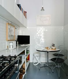 eat-in kitchen, TV on the counter, subway tile, art in the kitchen
