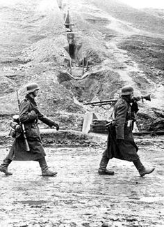 Two German soldiers walk past some hillside trenches, somewhere on the Eastern Front.
