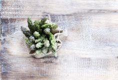 Bunches of asparagus lying on a wooden table by Wild Drago Shop on…