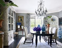 The dining room in Dave DeMattei and Patrick Wade's Los Angeles home features a crystal chandelier and ebonized table, both antiques from Guinevere; the chairs are by George Smith; the curtains are made of a Barclay Butera Home cotton print, and the carpet is by Ralph Lauren Home.  PHOTOGRAPHER: William Waldron