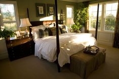 Bedroom decked out in darker hues, with rich dark wood four post bed frame and matching dresser, brown patterned ottoman, and green wall paint.