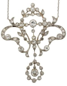 An Edwardian diamond pendant. Of garland form and set overall with graduated circular cut diamonds in white gold. Fitted case. On a fine link neck chain.