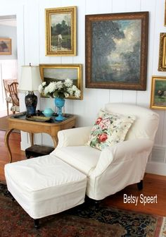 Crisp white slipcover.  Would it work in a house full of boys?  Maybe not, but I still like it. (Betsy Speert's Blog: Table Top Decorating Love the framed pictures)
