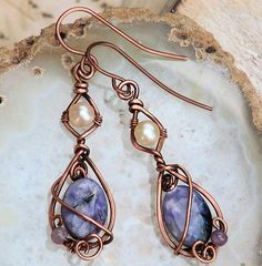 Wrapped Copper Earrings: Very rare Russian charoite is paired with silky freshwater pearls in these unusual copper earrings from Owl Hollow Studio. Artisan handmade, a teardrop and diamond shaped frame was forged with wire wrapped with swirls and loops of copper to hold the gemstones.