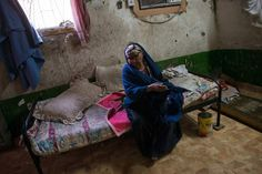 Selma Saleh, an impoverished Saudi woman, sits on her bed in her home in South Riyadh.