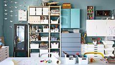 Een opbergwand met planken, geschilderde kasten, ladeblokken en bakken