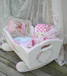 Doll cradle hand painted white with pink roses. A little bit shabby chic. Patchwork quilt of rose print fabrics, foam mattress, fitted sheet, and