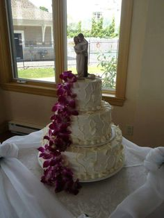 """This wedding cake is covered with our """"Petals and Vines"""" design. Love the cascade of purple mini orchids. #wedding #weddingcakes #orchids"""
