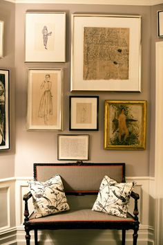 a perfect gray: collected art on a gray wall...upholstered bench with red trim
