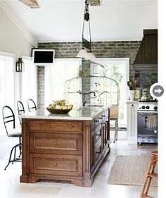 Mix of everything I love, brick, wood and painted cabinets w/ a bird cage too!