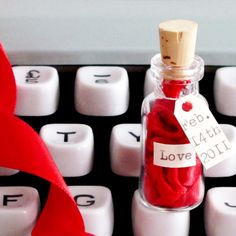 This is a message in a bottle with a unique twist! Remove the cork to reveal the personalised love note typed on satin ribbon.   The bottle is 45mm (approx 1.75 inches) high and the message on ribbon can be up to 35 words long.  To let us know what your preferred message, ribbon colour, date & name on the bottle just fill in the blanks over there on the right.  The bottle is presented in a black velvet bag inside a gift box. A matchstick is included for pushing the ribbon back into the bo…