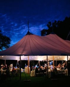 Tented fete at sunset, sparkling with strings of bistro lights