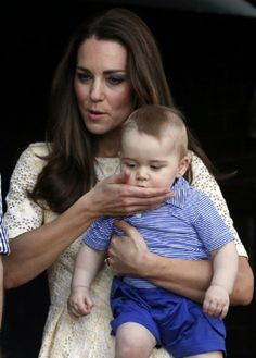 Catherine, Duchess of Cambridge wipes the mouth of her son Prince George after he had a tastes of a sticker, (yum!) during a 2014 visit to Sydney's Taronga Zoo