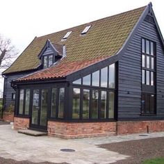 Black exterior on this barndominium conversion with lots of windows for a beautiful view. Black Shed, Black Barn, Modern Farmhouse Design, Modern Farmhouse Exterior, Shed Cabin, Brick Fireplace Makeover, Dark House, Lots Of Windows, Black Exterior