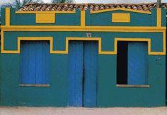 """""""O que dizem essas casas?"""", interroga Caetano Veloso, em texto escrito para a exposição de Anna Mariani no Centre Georges Pompidou, em Paris. """"Para mim, são coisas íntimas. Casas que conheço por dentro. Em Santo Amaro, onde nasci, no Recôncavo baiano, as pessoas pintam suas casas a cada fevereiro para as festas da padroeira: é como comprar um vestido novo. A cidade fica endomingada, como se fosse um cenário de teatro ingênuo, com todas as casas recém-pintadas"""", registra Caetano."""