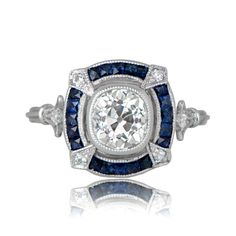 A beautiful Art Deco inspired engagement ring, starring an old mine cushion cut diamond, and encircled by a halo of sapphires and diamonds.