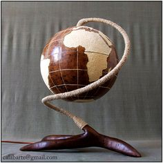 Website: calabarte.com/ Facebook: www.facebook.com/calabarte  TABLE LAMP VII – GLOBE The lamp is made from gourd brought from Senegal.  It is a precise model of the globe. Meridians and circles of latitude are marked every 20 degrees; the contours of the continents and islands are reconstructed accordingly. The land is marked by a deeper layer of white wood. The lamp has no holes other than the meridians and circles of latitude which allow light to pass trough them. The globe consists of two…