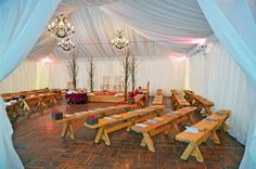 Natural wood benches create a beautiful seating arrangement for a ceremony under our tents.