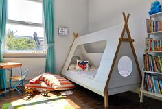 cuckooland bed - turquoise curtains - floor cushions - colourful desk - light box - tent bed - children's room - gender-neutral children's rooms - kids' room - boy's room - feature wallpaper - children's bookshelf - colourful children's room - wallpaper for children's room - go to your room!