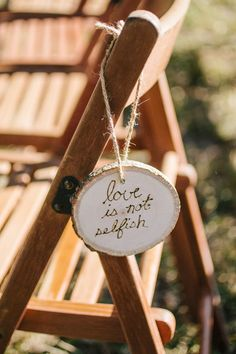 Wood slices tied to wedding ceremony chairs with verses from 1 Corinthians 13:4-7 {Riverland Studios}