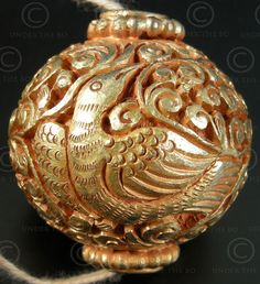 Engraved Buddhist beads- gilded brass beads, engraved with floral, mythical animals and volutes designs.