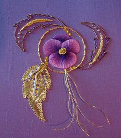 Goldwork pansy. The project is worked on a background of silk dupoini woven in purple and red. Predominantly, the purple shows up, but you can see the reddish highlights in the photo.