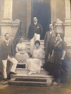 A família posando para a fotografia na entrada da casa da Avenida Paulista. À esquerda, Antonio Augusto, em pé na parte mais alta na escada, Clarimundo, no lado direto, Herculano. As duas mulheres sentadas: à esquerda, Maria Isabel, com sua filha, Antonia Eufrosina e a mulher de preto é Loutte, esposa de Clarimundo. Foto: acervo da família.
