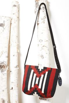 This crossbody bag is your tried and tested lightweight purse for every day and night. 'Aztec Charm' features a geometric Aztec design in classic red, black and white. It has an adjustable leather str