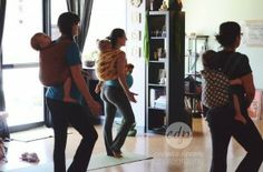 Three parents carrying their children on their backs in wraps while doing yoga.