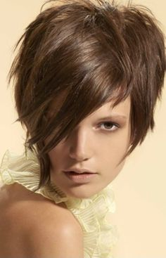 The hair is styled short at back, long at the sides and even longer at front. At top, the hair is  brushed in crisscross patterns with long bangs coming down at the front of the face.