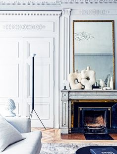 French living room with crown molding, pastel hues, and a fireplace