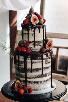 semi naked wedding cake with chocolate drip topped with fruit and berries