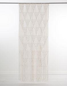 En gardin av vevet kvalitet i makramemönster.