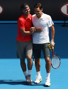 """Rafael Nadal of Spain and Roger Federer of Switzerland celebrate a point during the """"Rally For Relief"""" charity exhibition match ahead of the 2011 Australian Open at Melbourne Park on January 16, 2011 in Melbourne, Australia."""