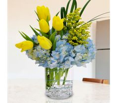 This stunning bouquet features blue hydrangea and yellow tulips artfully designed in a cylindrical glass vase, accented with gems at the bottom of the vase. A seasonal best seller, Springtime Bouquet is sure to put a smile on any lucky recipient's face!