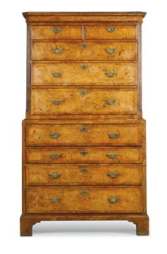 A George I walnut and feather banded secretaire chest on chest circa 1720 the top with a moulded cornice above two short and three long drawers below, the lower section with a secretaire drawer fitted with small drawers and pigeonholes, with three drawers below, on bracket feet