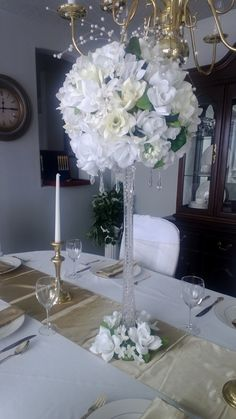 Eiffel Centerpiece white and cream roses, water beads filled the vase with light, pearls strands stream out