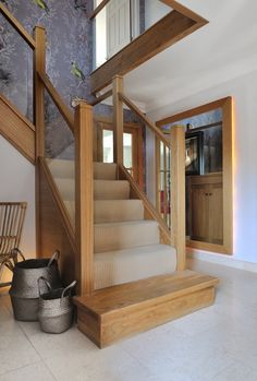 A centrally-positioned modern staircase with a mix of natural oak and glass with a half-landing turn and gallery landing.