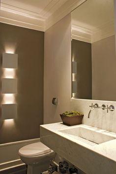 A arquiteta e decoradora Beatriz Dutra aplicou porcelanato Portobello no lavabo. Na parede, pintura com tinta látex Suvini em dois tons. O teto foi rebaixado com gesso, também pintado com látex. Já a bancada foi feita de mármore carrara, com cuba esculpida no próprio mármore. Os metais são da Deca, assim como o vaso sanitário. Para iluminar o ambiente, Beatriz escolheu arandelas da Wall Lamps