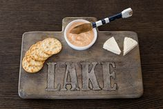 "Distressed mango wood board features inlaid cast aluminum ""LAKE"" message with recessed removable white ceramic ramekin and mango wood oar spreader. This 3-piece set makes for a great gift for a lake hostess. The solid wood board measures 7 1/2"" x 12"" 1/2"""