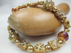 AN ELEGANT SHELL AND ACRYLIC BRACELET.   IT IS UNIQUE AND MAKES A LOVELY STATEMENT.  THIS STRETCH BRACELET HAS CREAM COLORED SQUARE SHELL BEADS WITH AMBER TONES.  GOLD ACRY...